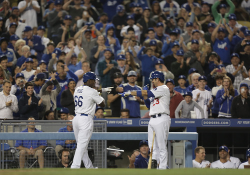 Los Angeles Dodgers Yasiel Puig (66) celebrates with Adrian Gonzalez after Puig homered during the sixth inning of their baseball game against the San Diego Padres, Tuesday, June 4, 2013, in Los Angeles. (AP Photo/Jason Redmond)