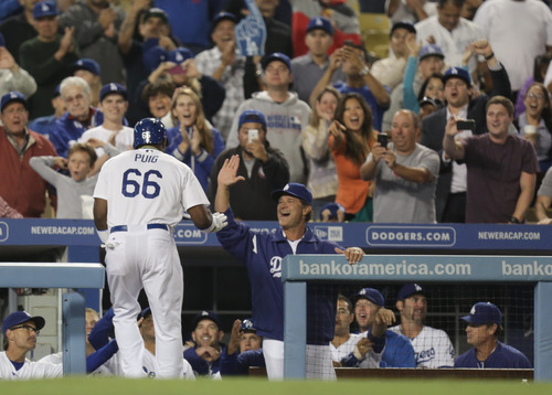 Los Angeles Dodgers Yasiel Puig (66) celebrates with manager Don Mattingly after Puig homered during the sixth inning of their baseball game against the San Diego Padres, Tuesday, June 4, 2013, in Los Angeles. (AP Photo/Jason Redmond)