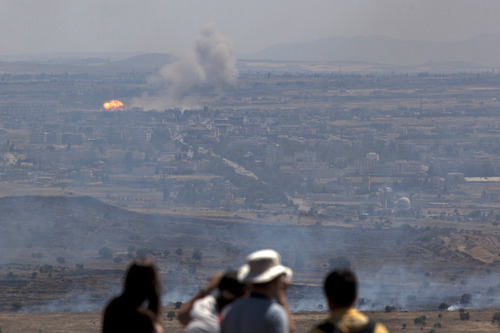 Israelis and tourists look at fire caused by fighting in Syria from an observation point on Mt. Bental in the Golan Heights, near the border between Syria and Israel, Friday, June 7, 2013. Syrian rebels on Thursday briefly captured a crossing point along a cease-fire line with Israel in the contested Golan Heights. (AP Photo/Sebastian Scheiner)