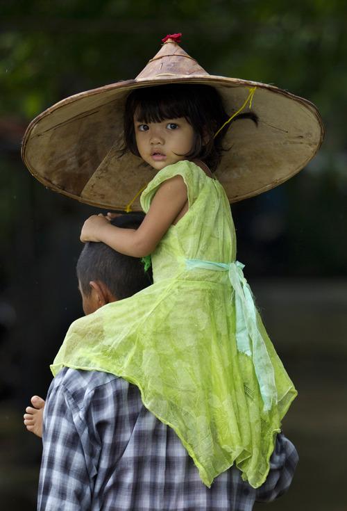A child is carried by an adult in Khanaung Chaung Wa village, southeast of Yangon Myanmar, Wednesday, June 5, 2013. (AP Photo/Gemunu Amarasinghe)