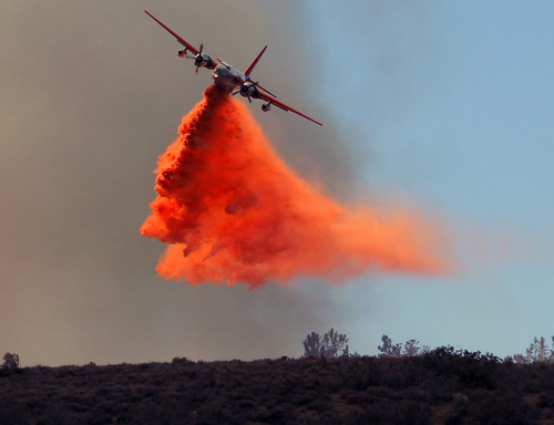 A plane drops fire retardant on a wildfire in Lancaster, Calif., Monday, June 3, 2013. Firefighters working in darkness doubled containment of a massive wildfire north of Los Angeles to 40 percent overnight, as cool, moist air moved in Monday to replace torrid weather. (AP Photo/Nick Ut)