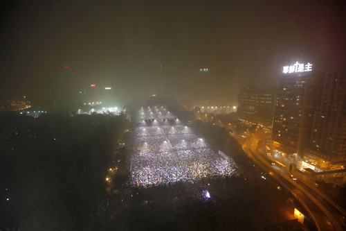 Tens of thousands of people attend a candlelight vigil in heavy rain at Victoria Park in Hong Kong Tuesday, June 4, 2013 to mark the 24th anniversary of the June 4th Chinese military crackdown on the pro-democracy movement in Beijing. (AP Photo/Kin Cheung)