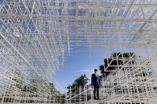 A broadcast journalists stands inside the Serpentine Gallery 2013 Pavilion, designed by Japanese architect Sou Fujimoto, in central London's Kensington Gardens, Tuesday, June 4, 2013. Occupying some 357 square-meters of lawn in front of the Serpentine Gallery, 41-year-old Fujimoto's structure of 20mm steel poles features a cafe and visitors will be encouraged to enter and interact with the piece in different ways. (AP Photo/Lefteris Pitarakis)