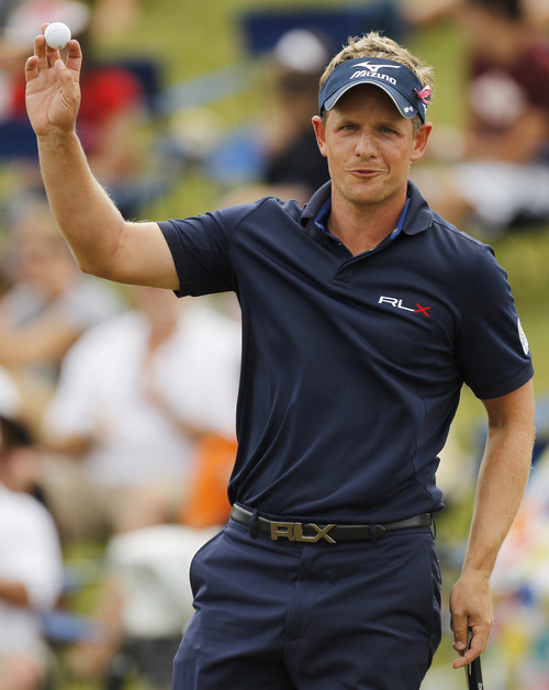 Luke Donald, of England, shows his ball on the 18th green during the final round of the Players Championship golf tournament at TPC Sawgrass, Sunday, May 13, 2012, in Ponte Vedra Beach, Fla. (AP Photo/Chris O'Meara)