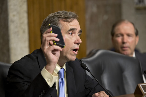 Senate Appropriations Committee member Sen. Jeff Merkley, D-Ore. holds up his Verizon cell phone as he asks a question of Gen. Keith B. Alexander, director of the National Security Agency, during the committee's hearing on cybersecurity and funding, Wednesday, June 12, 2013, on Capitol Hill in Washington. Sen. Tom Udall, D-N.M., watches at right.  It is the first public appearance by an NSA official since revelations that the electronic surveillance agency is sweeping up Americans' phone and Internet records in its quest to investigate terrorist threats. (AP Photo/J. Scott Applewhite)