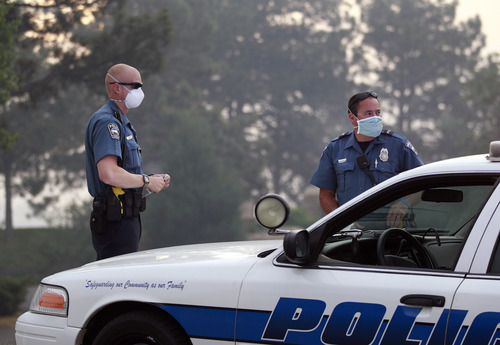 Colorado Springs police officers wear masks for smoke as they man a roadblock to an evacuated area of forest, ranches and residences, in the Black Forest wildfire area, north of Colorado Springs, Colo., on Thursday, June 13, 2013.  The blaze in the Black Forest area northeast of Colorado Springs is now the most destructive in Colorado history, surpassing last year's Waldo Canyon fire, which burned 347 homes, killed two people and led to $353 million in insurance claims. (AP Photo/Brennan Linsley)