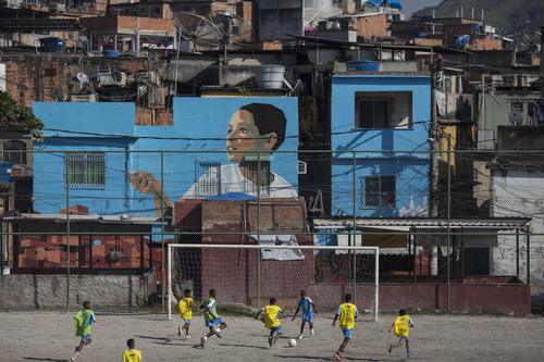 In this June 7, 2013 photo, youth play soccer in the Vila Cruzeiro slum in Rio de Janeiro, Brazil. With the Confederations Cup opening this week and the World Cup one year away, all eyes are on Brazil, where football is arguably played with more passion and art than anywhere. (AP Photo/Felipe Dana)