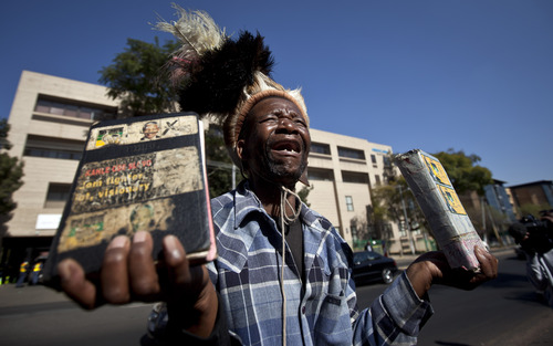 Wellwisher Daniel Sello cries out his thanks to Nelson Mandela in front of the Mediclinic Heart Hospital where he is being treated in Pretoria, South Africa Thursday, June 13, 2013. Former South African President Nelson Mandela is spending a sixth day in the hospital and while there was no immediate update on his health Thursday, President Jacob Zuma on Wednesday reported that Mandela was responding better to treatment for a recurring lung infection. (AP Photo/Ben Curtis)