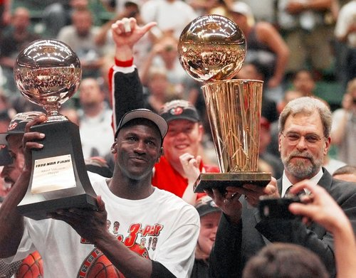 Chicago Bulls' Michael Jordan, left, holds the Most Valuable Player trophy as coach Phil Jackson holds the NBA Championship trophy after the Bulls defeated the Utah Jazz 87-86 in Game 6 of the NBA Finals in Salt Lake City, Sunday, June 14, 1998. (AP Photo/Jack Smith)