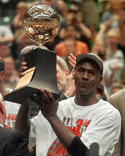 Series MVP Michael Jordan holds the MVP trophy after the Chicago Bulls defeated the Utah Jazz 87-86 in Game 6 of the NBA Finals in Salt Lake City, Sunday, June 14, 1998. (AP Photo/Jack Smith)