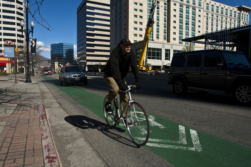 Photo by Chris Detrick | The Salt Lake Tribune  A man rides his bike along 200 South Wednesday April 27, 2011.  Salt Lake City proposing a 200 South bicycle greenway with new medians in the middle of the street with a bike and pedestrian path between the trees from 200 South to 1300 South, at the University of Utah.