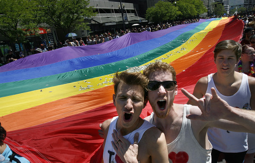 Scott Sommerdorf   |  The Salt Lake Tribune Nico Ridiuejo, left, and Matt Petersen, cheer while helping to carry the rainbow flag at the end of the Utah Pride Festival's Gay Pride Parade through the streets of downtown Salt Lake City, Sunday, June 2, 2013.