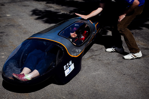 In this Tuesday, June 12, 2013 photo, BYU student Eric Wilcox, right, taps the canopy of his team's supermileage vehicle as driver Caroline Sorensen prepares to drive it during a demonstration at LaVell Edwards Stadium in Provo, Utah. (AP Photo/The Daily Herald, Mark Johnston)
