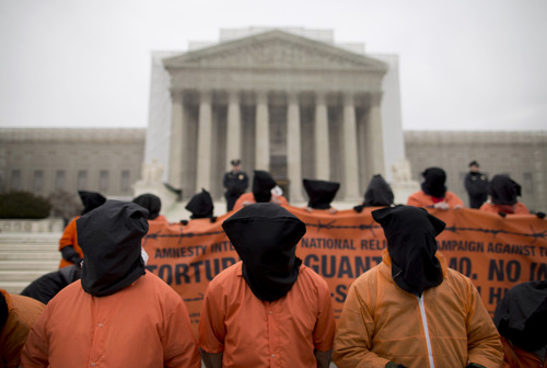 FILE - This Jan. 11,2013 file photo shows demonstrators, dressed as detainees, protest against the U.S. military detention facility in Guantanamo Bay, Cuba, in front of the U.S. Supreme Court in Washington. The Supreme Court might eventually need to decide how much free speech the Supreme Court can tolerate. A federal judge throws out a law barring protest banners and processions on the high court's grounds, rulings it's so broad it could criminalize preschool students parading on a field trip. (AP Photo/ Evan Vucci, File)