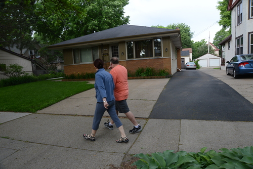 People walk past the home in Minneapolis, Minn., where 94-year-old Michael Karkoc lives, Friday, June 14, 2013.  Karkoc, a top commander of a Nazi SS-led unit accused of burning villages filled with women and children, lied to American immigration officials to get into the United States and has been living in Minnesota since shortly after World War II, according to evidence uncovered by The Associated Press. He told American authorities in 1949 that he had performed no military service during World War II, concealing his work as an officer and founding member of the SS-led Ukrainian Self Defense Legion and later as an officer in the SS Galician Division, according to records obtained by the AP through a Freedom of Information Act request. (AP Photo/The Star Tribune, Richard Sennott)  MANDATORY CREDIT; ST. PAUL PIONEER PRESS OUT; MAGS OUT; TWIN CITIES TV OUT