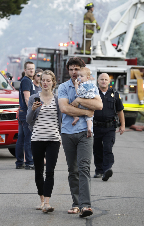 George Frey  |  Special to the Tribune A couple and their baby evacuates as a fast moving brush fire moves through a neighborhood in Provo, Utah on June 13, 2013.