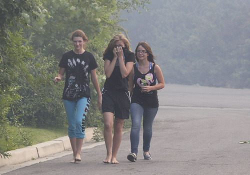 George Frey  |  Special to the Tribune Three girls evacuate as a fast moving brush fire moves through a neighborhood in Provo, Utah on June 13, 2013.