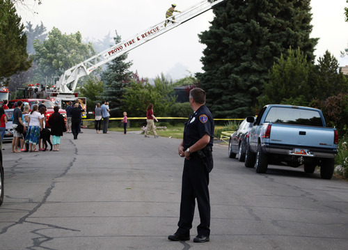 George Frey  |  Special to the Tribune A provo police officer closes a street as a fast moving brush fire moves through a neighborhood in Provo, Utah on June 13, 2013.