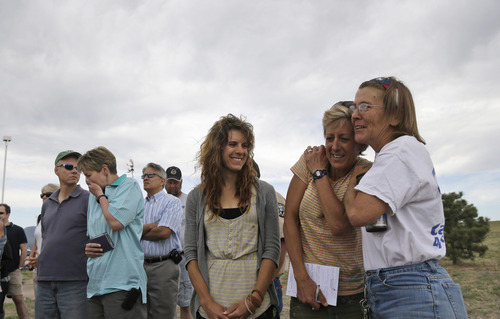 Nancy Bradley, right, a resident of Black Forest, Colo., hugs fellow evacuee Jenny Abernathy, second from right, as Rebecca Abernathy, third from right, Jenny's daughter, watches while listening to an update on the Black Forest Fire in Colorado Springs, Colo., Friday, June 14, 2013. Firefighters held the line Friday on the Black Forest Fire, in which two people were killed as they tried to escape and 379 homes were destroyed. (AP Photo/Marcio Jose Sanchez)