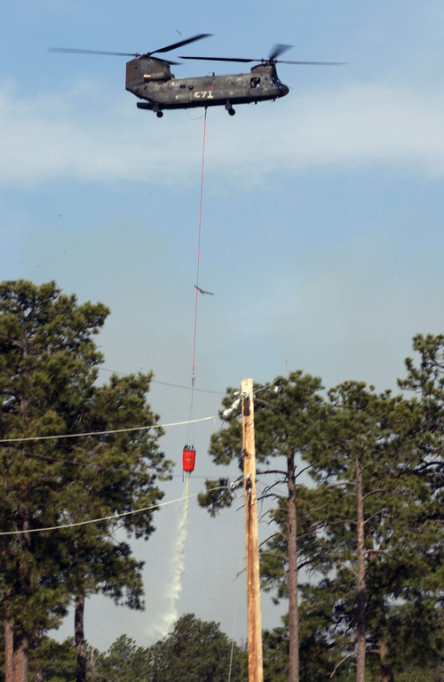 A U.S. Army Chinook helicopter drops a load of water on the Black Forest wildfire, north of Colorado Springs, Colo., on Thursday, June 13, 2013. According to officials, at least 360 homes have been burned, and at least 38,000 people have been evacuated since the fire began earlier in the week. (AP Photo/Brennan Linsley)