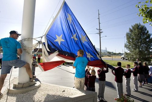 Paul Fraughton  |  The Salt Lake Tribune Children from Challenger School help a crew Friday from Colonial Flag Company in Sandy raise their 30-by-60-foot American flag. Two huge American flags were raised simultaneously at the corporate headquarters of Colonial Flag and Challenger School.