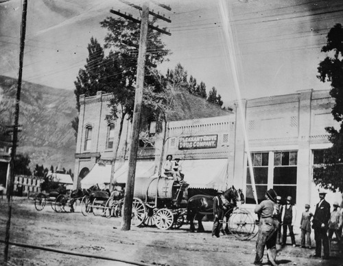 Tribune Archives Pleasant Grove's Main street, about 1906, showing the fire department's hose car and tank wagon: The corner building is the early Pleasant Grove bank.