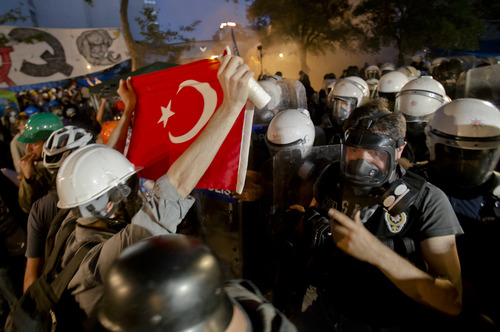 Protesters try to resist the advance of riot police in Gezi park in Istanbul, Turkey, Saturday, June 15, 2013. Protesters will press on with their sit-in at an Istanbul park, an activist said Saturday, defying government appeals and a warning from Prime Minister Recep Tayyip Erdogan for the two-week standoff that has fanned nationwide demonstrations to end. (AP Photo/Vadim Ghirda)