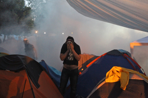 A protester reacts as police throw tear gas among tents during an  operation to evacuate the Gezi Park of Taksim Square in Istanbul,   Saturday, June 15, 2013.  Protesters will press on with their sit-in at an Istanbul park, an activist said Saturday, defying government appeals and a warning from Prime Minister Recep Tayyip Erdogan for the two-week standoff that has fanned nationwide demonstrations to end. (AP Photo/Thanassis Stavrakis)