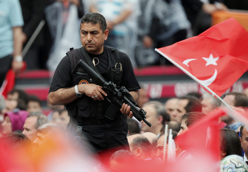 A special security man watches as Turkish Prime Minister Recep Tayyip Erdogan addresses a party rally outside Ankara, Turkey, Saturday, June 15, 2013. Erdogan said Friday he has asked a small delegation of protesters to convince those occupying a park to withdraw, adding that he is hopeful their protest action would end soon.(AP Photo/Burhan Ozbilici)