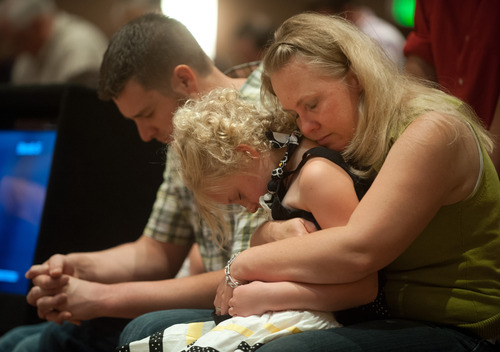 Lara Stern, right, prays with her daughter, Alana, 8, and husband Samuel Stern Sunday, June 16, 2013 during a community prayer and praise worship service at First Baptist Church on Black Forest Road northeast of Colorado Springs, Colo. The Stern family and at least ten other families at the church lost their homes to the Black Forest fire. (AP PHOTO/THE GAZETTE,MARK REIS)