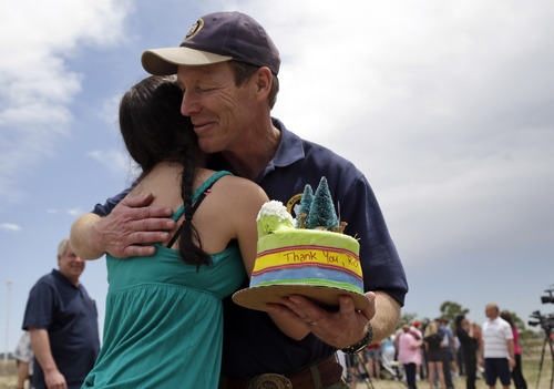 Incident commander Rich Harvey, right, hugs  Colorado Springs resident Nikki Connon after receiving a cake from Connon to thank him for his efforts in battling the Black Forest Fire in Colorado Springs, Colo., Sunday, June 16, 2013. (AP Photo/Marcio Jose Sanchez)