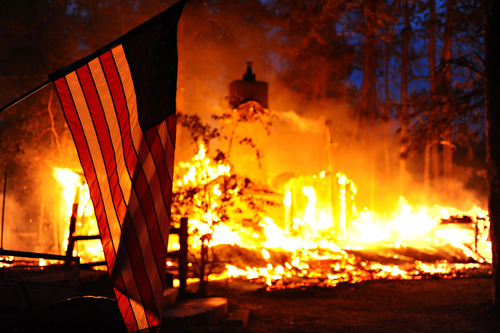 In this Tuesday, June 12, 2013 photo, released Saturday, June 15, 2013, by the U.S. Air Force, an American flag hangs in front of a burning structure in the Black Forest, a thickly wooded rural region north of Colorado Springs, Colo. Authorities reported early Saturday that 473 houses had been incinerated. That compares with a report of a little over 400 just a few hours earlier.  (AP Photo/U.S. Air Force, Master Sgt. Christopher DeWitt)