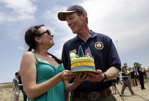 Incident commander Rich Harvey, right, gets a cake from Colorado Springs resident Nikki Connon thanking for his efforts in battling the Black Forest Fire in Colorado Springs, Colo., Sunday, June 16, 2013.  Firefighters worked to get more people evacuated by Colorado's most destructive wildfire back home Sunday by digging up and extinguishing hot spots to protect homes still standing near Colorado Springs.   (AP Photo/Marcio Jose Sanchez)