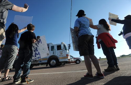 People line Old Ranch Road as they cheer for the firefighters returning from a shift fighting the Black Forest Fire Sunday morning, June 16, 2013, outside the fire camp at Pine Creek High School in Colorado Springs, Colo.   Firefighters worked to get more people evacuated by Colorado's most destructive wildfire back home Sunday by digging up and extinguishing hot spots to protect homes still standing near Colorado Springs.  (AP Photo/The Gazette, Christian Murdock)  MAGS OUT