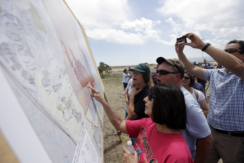 Residents look at a map of the Black Forest Fire after a press briefing in Colorado Springs, Colo., Saturday, June 15, 2013. The number of homes destroyed in Colorado's most destructive wildfire ever continues to rise. Authorities reported early Saturday that 473 houses had been incinerated. That compares with a report of a little over 400 just a few hours earlier. (AP Photo/Marcio Jose Sanchez)