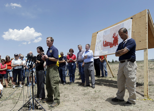 Incident commander Rich Harvey, center, talks about the progress of the Black Forest Fire in Colorado Springs, Colo., Saturday, June 15, 2013. The number of homes destroyed in Colorado's most destructive wildfire ever continues to rise. Authorities reported early Saturday that 473 houses had been incinerated. That compares with a report of a little over 400 just a few hours earlier.(AP Photo/Marcio Jose Sanchez)
