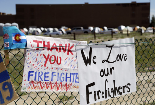 A sign thanks firefighters for their efforts battling the Black Forest Fire at a fire camp in Colorado Springs, Colo., Sunday, June 16, 2013. (AP Photo/Marcio Jose Sanchez)