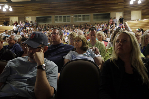 Black Forest, Colo., resident Carol Sisk, center, is embraced by her husband Marc during an informational meeting on the progress of the Black Forest Fire at Palmer Ridge High School in Monument, Colo. on Saturday, June 15, 2013. (AP Photo/Marcio Jose Sanchez)