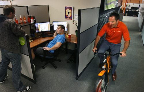 Scott Sommerdorf      The Salt Lake Tribune One of the original founders of OrangeSoda, Derek Miner, demonstrates the use of one of the orange bikes available to employees, as he rides past Josh Brereton, center, a popsite specialist, as he has a meeting with Brent Blackwood, left, at Brereton's desk at OrangeSoda in American Fork, Wednesday, June 5, 2013. Thirty-five percent of all jobs created in Utah since 2010 have been created between 10600 South in Salt Lake County and Provo/Orem. Most have been high technology jobs like the ones at OrangeSoda which has about 200 employees. The company helps clients with online marketing. It employs people in all sorts of occupations, including software engineers, web designers and sales people. Wednesday, June 5, 2013.