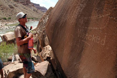 Francisco Kjolseth  |  The Salt Lake Tribune Julian Springer overlooks the note etched into the rock above one of the Cataract Canyon rapids that reads Wrecked C.M Wright 1892 during a trip in July 2012.