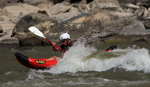 Francisco Kjolseth  |  The Salt Lake Tribune River guide Julian Springer gets a shot at playing with the inflatable kayak in the first rapid of Cataract Canyon in July of 2012.