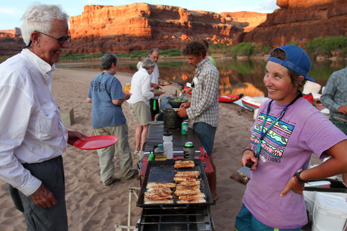 Francisco Kjolseth  |  The Salt Lake Tribune Bob Hollingsworth flatters the cook as river guide Lauren Wood serves up fish steaks in the setting sun along the shores of the Colorado River in Canyonlands Utah in July 2012.