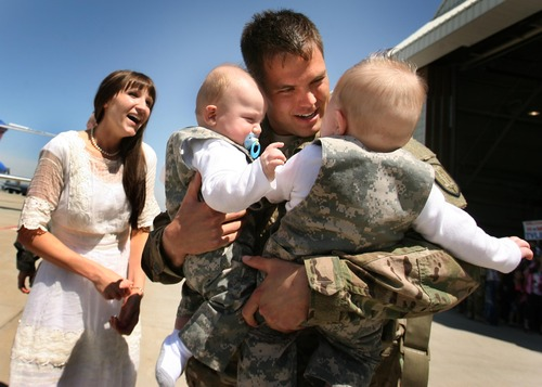 Leah Hogsten     The Salt Lake Tribune Sgt. Phillip Bassett on Thursday holds his 6-month-old twin sons, Noelan and Hudson, for the first time as his wife, Kristina Bassett, watches. Twenty-seven babies, 23 single births and two sets of twins were born to wives of returning soldiers of the Utah National Guard's 624th Engineer Company, 1457th Engineer Battalion, during their 10-month deployment to Afghanistan.
