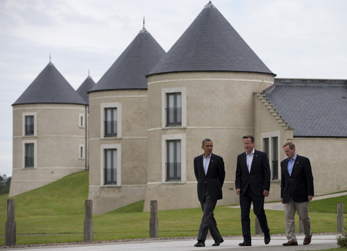 President Barack Obama walks with British Prime Minister David Cameron, center, and Irish Prime Minister Enda Kenny at the site of the G-8 summit in Enniskillen, Northern Ireland, Tuesday, June 18, 2013. The final day of the G-8 summit of wealthy nations is ending with discussions on globe-trotting corporate tax dodgers, a lunch with leaders from Africa, and suspense over whether Russia and Western leaders can avoid diplomatic fireworks over their deadlock on Syria's civil war. (AP Photo/Evan Vucci)
