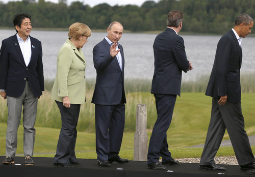 G-8 leaders from left, Japan's Prime Minister Shinzo Abe, German Chancellor Angela Merkel, Russian President Vladimir Putin, British Prime Minister David Cameron and US President Barack Obama leave the podium after a group photo opportunity during the G-8 summit at the Lough Erne golf resort in Enniskillen, Northern Ireland, on Tuesday, June 18, 2013. The final day of the G-8 summit of wealthy nations is ending with discussions on globe-trotting corporate tax dodgers, a lunch with leaders from Africa, and suspense over whether Russia and Western leaders can avoid diplomatic fireworks over their deadlock on Syria's civil war. (AP Photo/Lefteris Pitarakis)