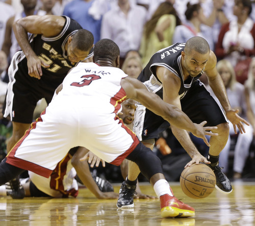 San Antonio Spurs point guard Tony Parker (9) moves the ball against Miami Heat shooting guard Dwyane Wade (3) during overtime of Game 6 of the NBA Finals basketball game, Wednesday, June 19, 2013 in Miami. The Miami Heat won 103-100 in overtime.(AP Photo/Lynne Sladky)