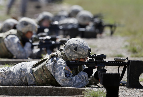 FILE - In this Sept. 18, 2012 file photo, female soldiers from 1st Brigade Combat Team, 101st Airborne Division train on a firing range while testing new body armor in Fort Campbell, Ky., in preparation for their deployment to Afghanistan. Women may be able to begin training as Army Rangers by mid-2015, and as Navy SEALs a year later under broad plans Defense Secretary Chuck Hagel is approving that would slowly bring women into thousands of combat jobs, including those in the country's elite special operations forces, according to details of the plans submitted to Hagel that were obtained by The Associated Press.   (AP Photo/Mark Humphrey, File)