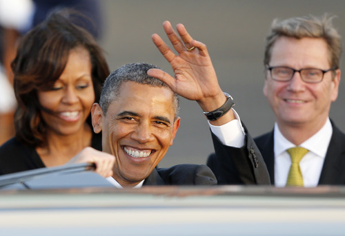 US President Barack Obama waves after disembarking from Air Force One at the Tegel airport in Berlin Tuesday, June 18, 2013. Obama arrived for a two-day official visit to Germany. At right German Foreign Minister Guido Westerwelle. (AP Photo/Michael Probst)