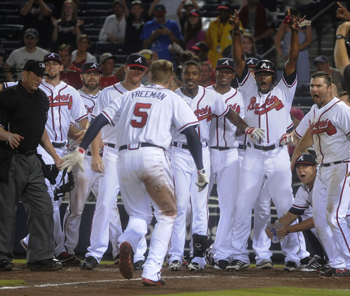 Atlanta Braves' Freddie Freeman (5) approaches home plate as team mates wait to greet him during his two run home run to win the baseball game against the New York Mets during the ninth inning, Monday, June 17, 2013, in Atlanta. Atlanta won 2-1. (AP Photo/John Amis)