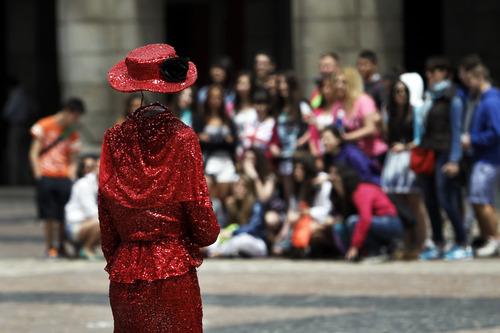 A woman who performs for money approaches a group of visitors in Madrid, Spain, Tuesday, June 18, 2013. Spain has been in recession for the best part of the past four years as the economy battles to recover from the collapse. (AP Photo/Andres Kudacki)
